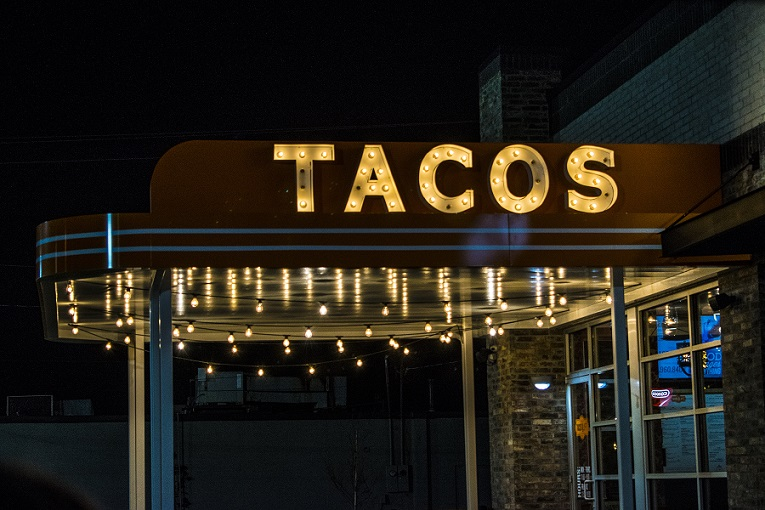 A restaurant sign for Tacos lit up at night